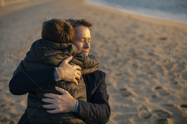 Father hugging son on the beach