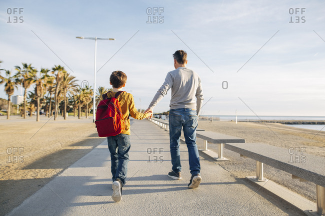 Father and son walking on beach promenade