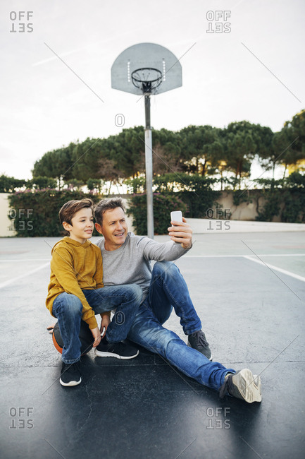 Father and son sitting on basketball outdoor court taking a selfie
