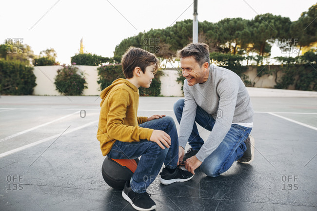 Father lacing son's shoe on basketball outdoor court