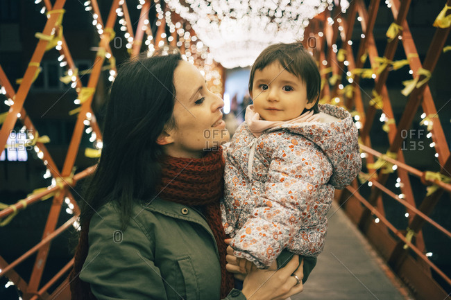 Mother and baby girl on bridge with lights at Christmas
