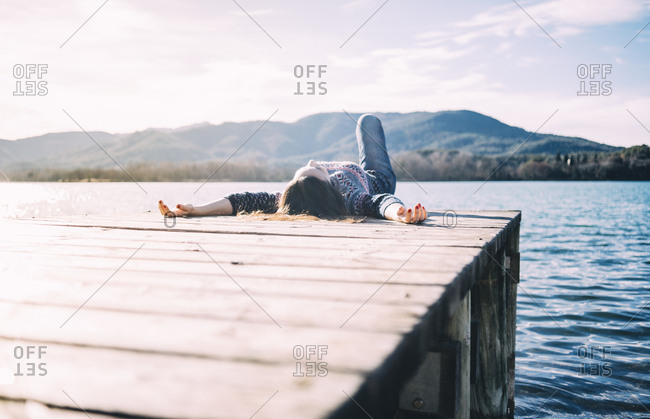 Woman resting on a wooden jetty at a lake