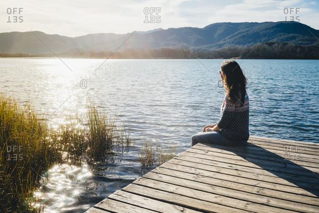Woman sitting on a wooden platform at a lake at sunset