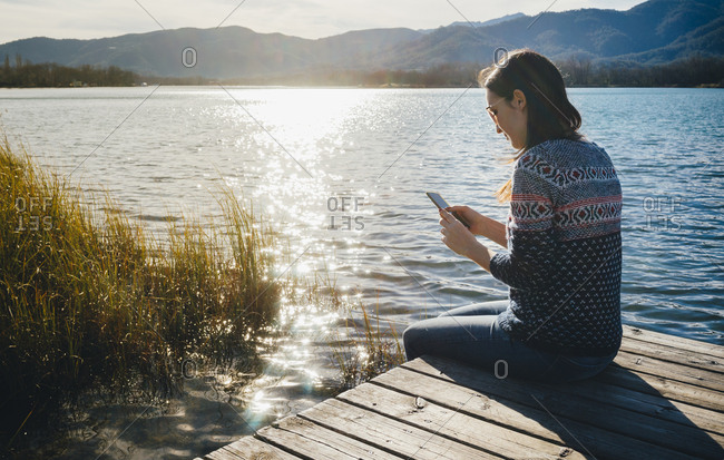Woman sitting on a wooden platform at a lake at sunset- using smartphone
