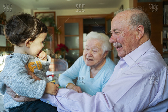 Great-grandparents playing with baby girl at home