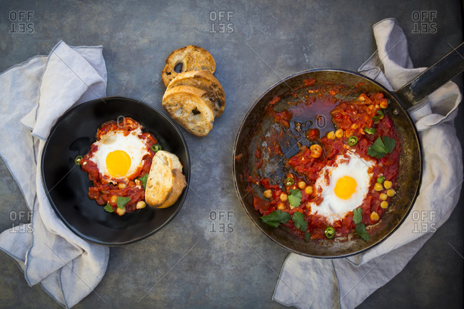 Shakshouka with chick peas in pan and slices of roasted baguette