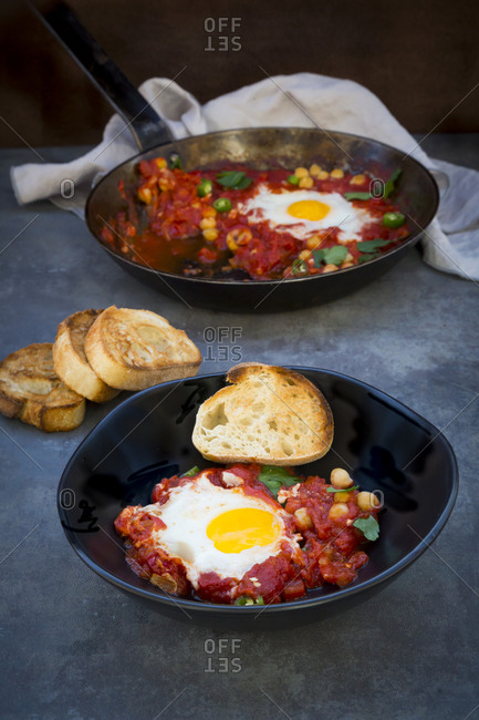 Shakshouka with chick peas in pan and slices of baguette