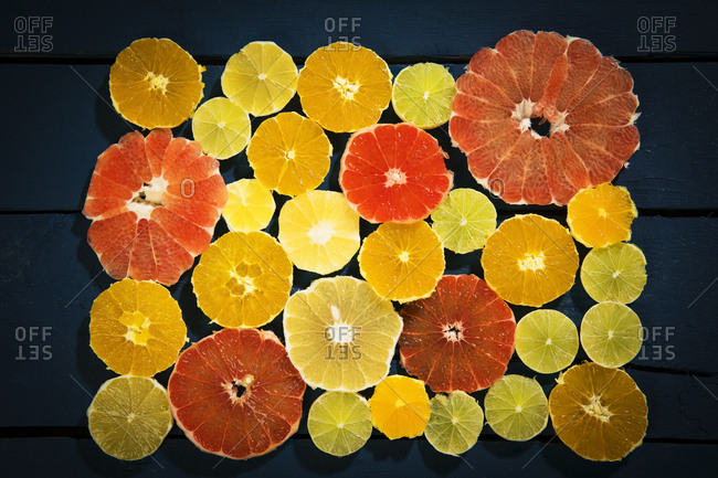 Sliced citrus fruits on black ground