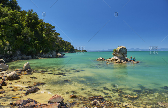 New Zealand- South Island- Abel Tasman National Park- tourists on rock in the sea
