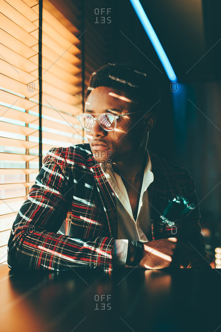 Portrait of fashionable young man wearing checkered suit coat looking out of window
