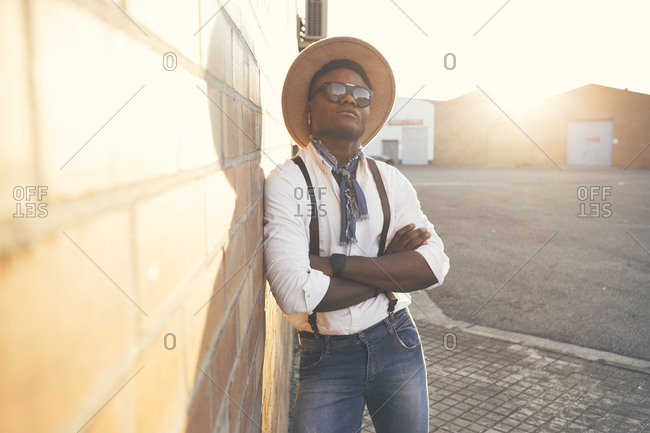 Portrait of cool young man wearing hat and sunglasses leaning against wall