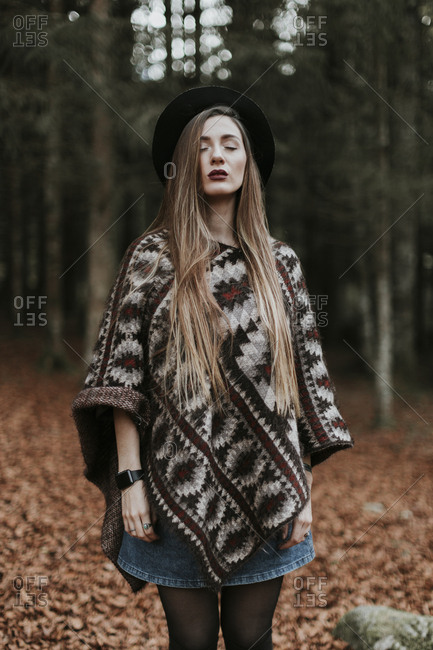 Portrait of young woman wearing hat and poncho standing in autumnal forest