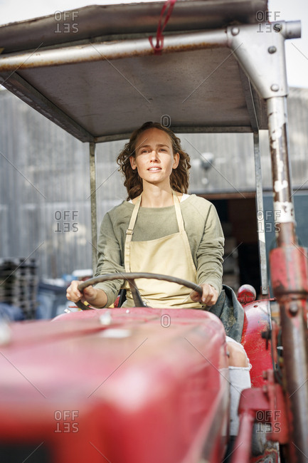 Portrait of confident woman driving a tractor