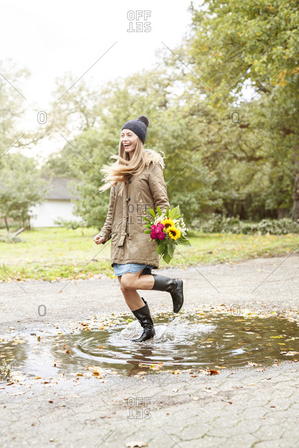 Happy young woman holding bunch of flowers jumping in puddle