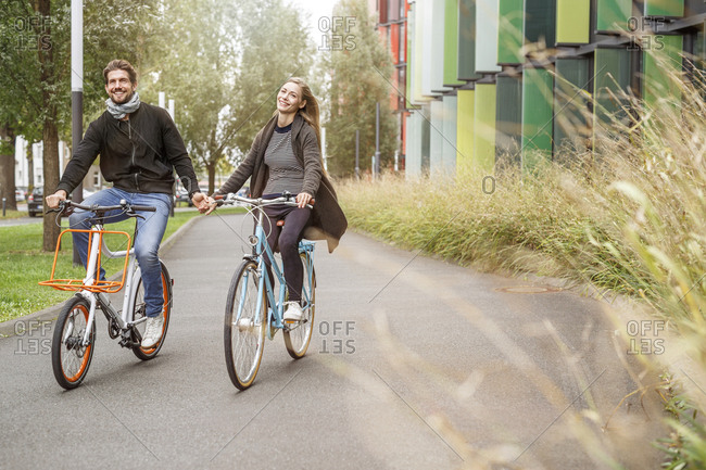 Happy couple riding bicycle hand in hand on a lane