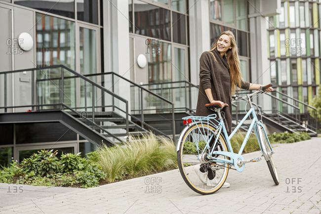 Smiling woman with bicycle standing in front of a building