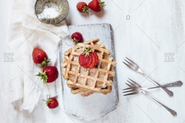 Belgian waffles with strawberries and powdered sugar