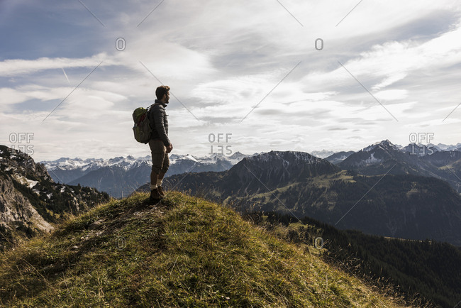 Austria- Tyrol- young man standing in mountainscape looking at view
