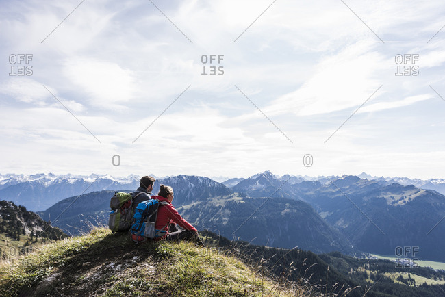 Austria- Tyrol- young couple sitting in mountainscape looking at view