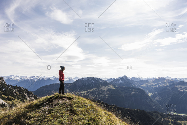 Austria- Tyrol- young woman standing in mountainscape looking at view