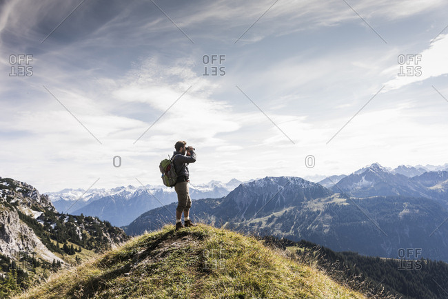Austria- Tyrol- young man standing in mountainscape looking at view with binoculars