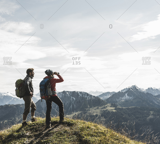 Austria- Tyrol- young couple standing in mountainscape looking at view