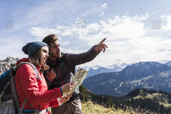 Austria- Tyrol- young couple with map in mountainscape looking around