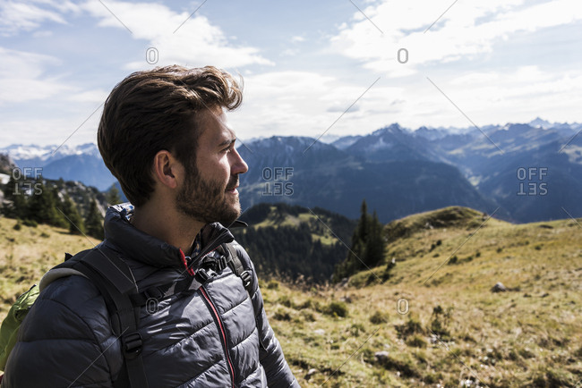 Austria- Tyrol- portrait of young man in mountainscape looking at view
