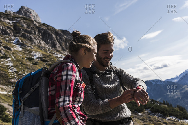 Austria- Tyrol- smiling young couple looking at watch in mountainscape