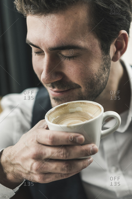 Relaxed young man drinking cup of coffee