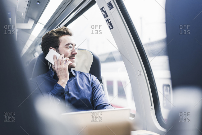 Smiling businessman in train on cell phone