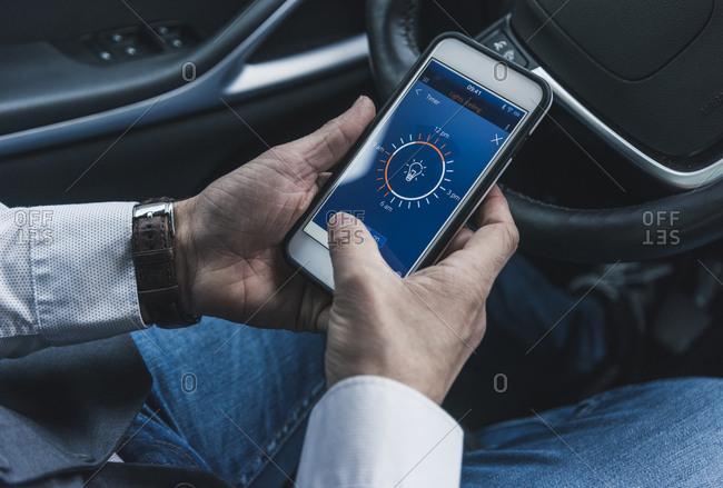 Man in car adjusting smart home device via smartphone