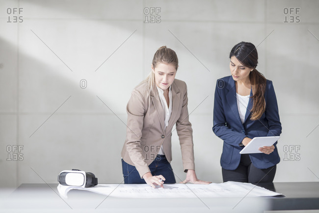 Two young women with tablet and VR glasses working on blueprint in office