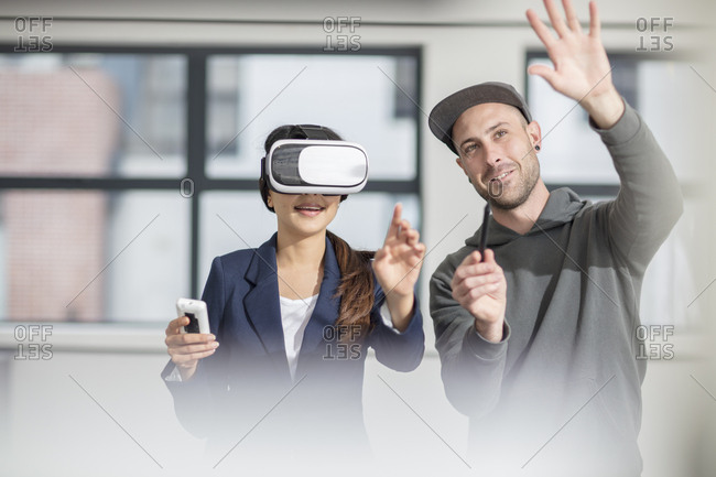 Man instructing businesswoman wearing VR glasses in office