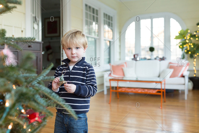 Young blonde boy decorating Christmas tree in living room