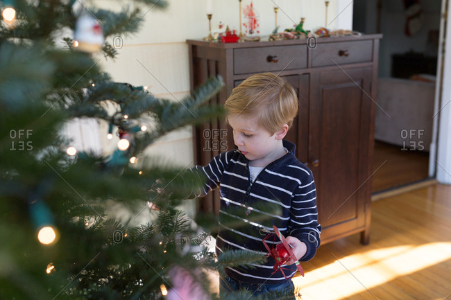 Little boy helping decorate Christmas tree