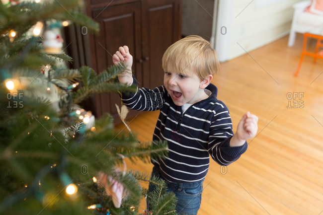 Excited toddler hanging Christmas ornaments at home