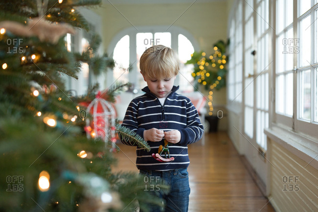 Boy arranging Christmas tree ornaments