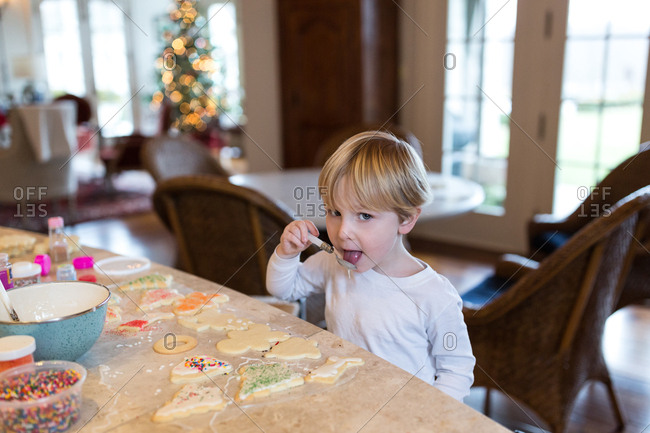 Boy tasting icing while making Christmas cookies