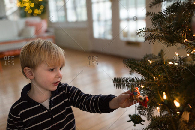 Little boy decorates christmas tree