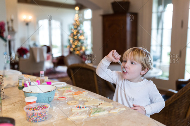 Little boy with spoon making holiday cookies
