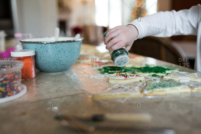Child's hand pouring sugar sprinkles on decorated holiday cookies