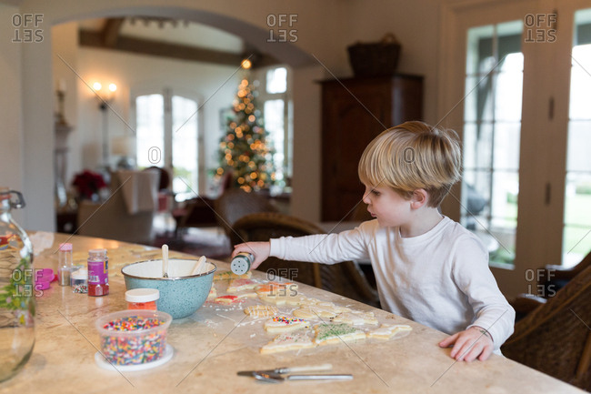 Boy pouring sprinkles on holiday sugar cookies