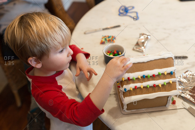 Little boy placing pieces of candy on gingerbread house