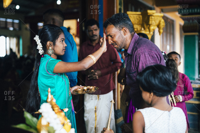 Hapatule, Sri Lanka - February 3, 2018: Guest is greeted with a tilaka on the forehead on arriving at a wedding at a small temple