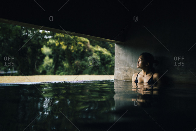 Kandy, Sri Lanka - February 4, 2018: A young Asian woman in a spa pool at Santani Resort near the Knuckles Mountain Range