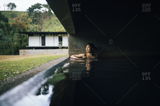 Kandy, Sri Lanka - February 4, 2018: Young woman looking out over the jungle and the mountains from the spa pool at Santani Resort