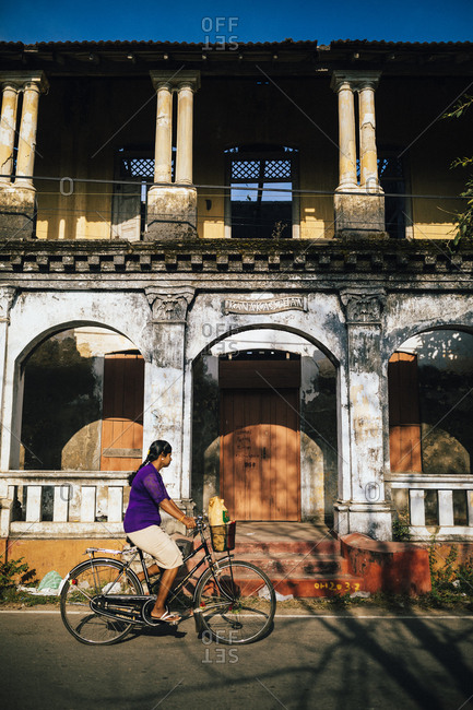 Jaffna, Sri Lanka - February 8, 2018: Woman riding bicycle past old colonial building