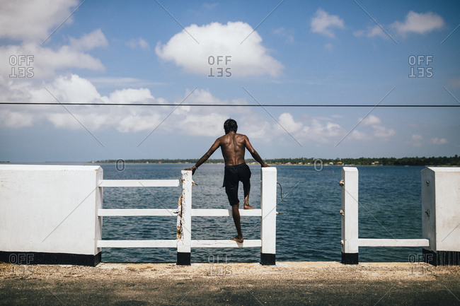 Jaffna, Sri Lanka - February 8, 2018: Rearview of fisherman standing on broken railing looking out over the sea on the Jaffna Peninsula