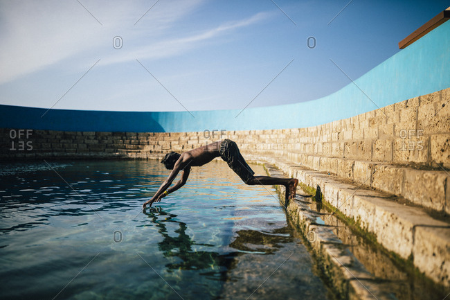 Jaffna, Sri Lanka - February 8, 2018: Young boy diving into clear waters of Keerimalai Springs
